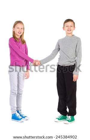 Happy boy and girl standing and shaking hands. Full length studio shot isolated on white.