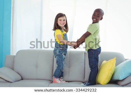 Happy boy and girl standing up on the couch