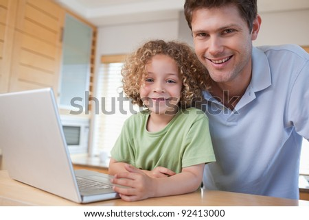 Happy boy and his father using a notebook in their kitchen - stock photo