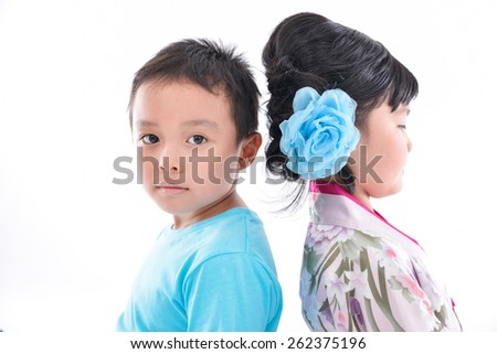 Happy boy and little girl standing back to back isolated - stock photo
