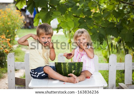 happy boy and little girl with watermelon lying