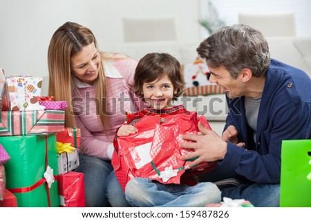 Happy boy and parents opening Christmas present at home