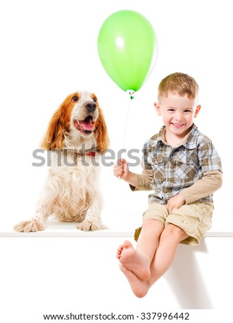 Happy boy and Russian Spaniel playing with a balloon, isolated on white background