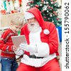 Happy boy and Santa Claus using digital tablet in courtyard - stock photo