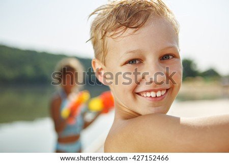 Happy boy at the lake on the holidays playing with a squirt gun