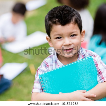 Happy boy at the school holding a notebook and smiling - stock photo