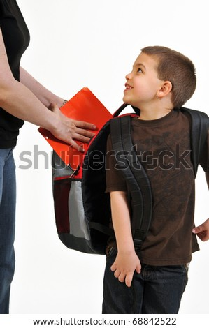 Happy boy being helped by mom placing folder in his backpack. He is smiling, looking back, showing gratitude to mom for helping him. Set over a white background. - stock photo