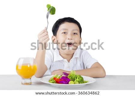 Happy boy eating broccoli with fork isolated on white background - stock photo