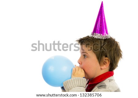 happy boy having a party,blowing up a balloon. - stock photo