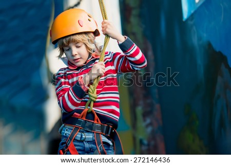 Happy boy having fun and playing at adventure park, holding ropes and climbing wooden stairs - stock photo