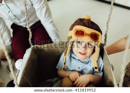 Happy boy having fun in handmade basket of air balloon. Child play at home with parents. Young pilot indoors. Boy in hat like a helmet looking at camera. - stock photo