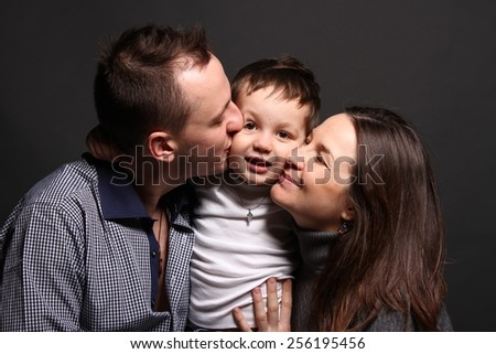 Happy boy having the attention of his parents kissing him - love concept - stock photo