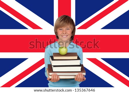 Happy Boy Holding Stack Of Books With Apple Against British Flag - stock photo