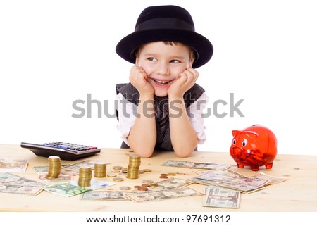 Happy boy in black hat and tie at the table with pile of money, isolated on white - stock photo