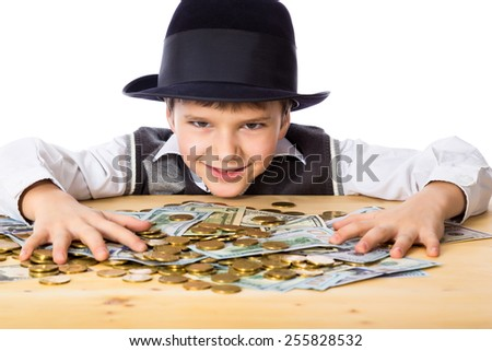 Happy boy in black hat with money on the table, isolated on white - stock photo