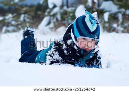 Happy boy in blue clothes lying in the snow - stock photo
