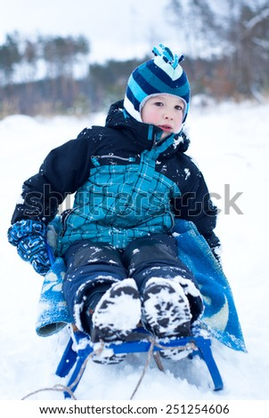 Happy boy in blue clothes sledding in snowing winter - stock photo