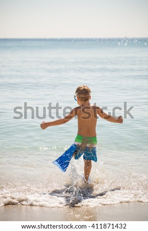Happy boy in flippers running into ocean on a sunny day. Child going to swim in the sea. Vacations. Activities for child on the beach. Joy and happiness. - stock photo