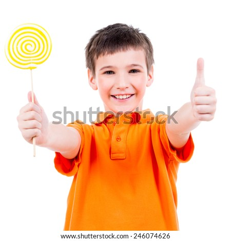 Happy boy in orange t-shirt with colored candy showing thumbs up sign - isolated on white. - stock photo