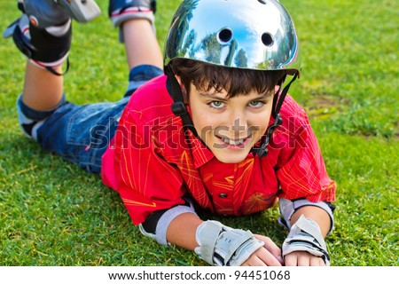 happy boy in roller blades grear laying on grass - stock photo