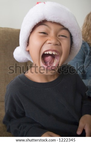 Happy boy in santa hat with mouth wide open showing inside of mouth