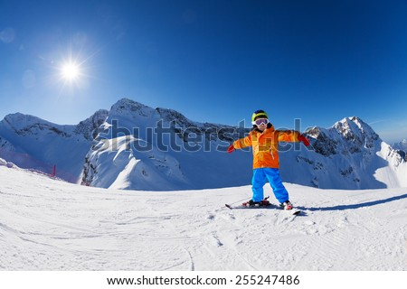 Happy boy in ski mask with arms apart skiing alone