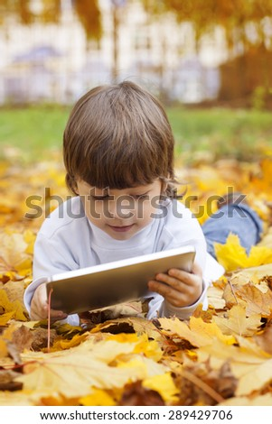 happy boy in the park using a tablet PC - stock photo