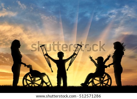 Happy boy in wheelchair and boy standing with crutches disabled person and nurses sunset. Happy disabled child concept