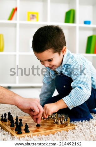 Happy boy is playing chess in living room.