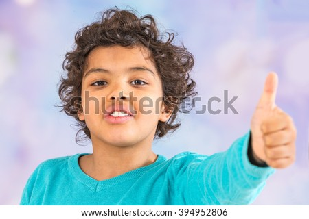 happy boy is showing his left thumb up - stock photo