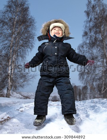 happy boy jump in winter outdoors - stock photo