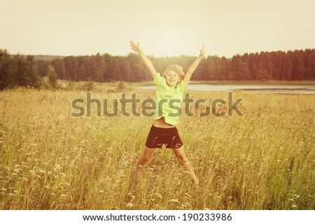Happy boy jumping on a summer field. - stock photo