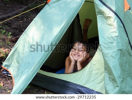 happy boy looking from camping tent - stock photo