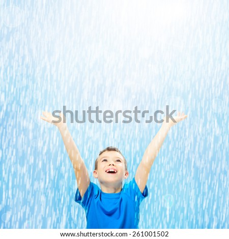 Happy boy looking up with his hands up in the rain - stock photo