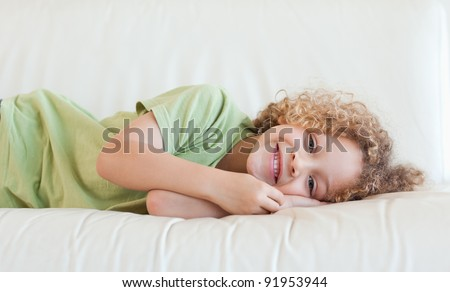 Happy boy lying on a sofa while looking at the camera - stock photo