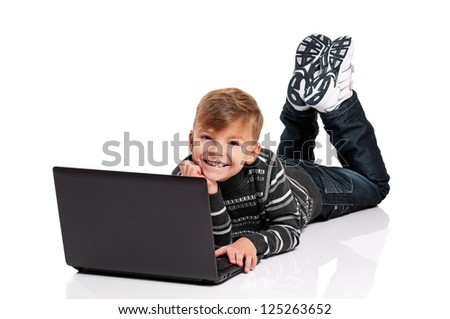 Happy boy lying on floor with laptop on white background - stock photo