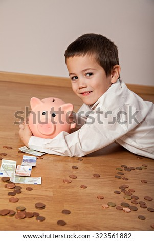 Happy boy lying on the floor with money and a piggy bank  - stock photo