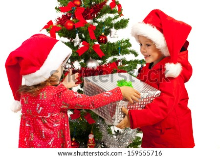 Happy boy offering Christmas present to little girl near tree