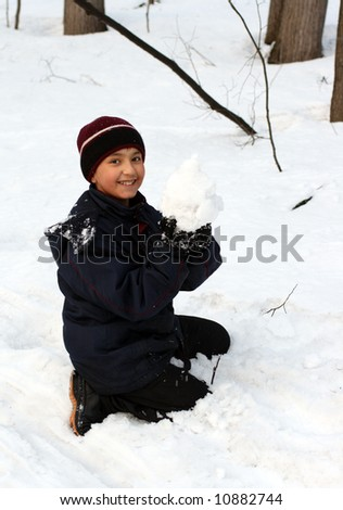 happy boy on snow with snowball in the winter forest - stock photo