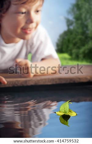 happy boy play in leaf ship (focus on ship) - stock photo