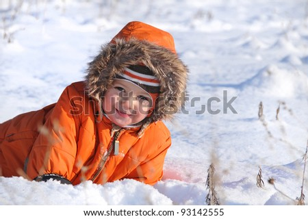 happy boy playing in the snow - stock photo