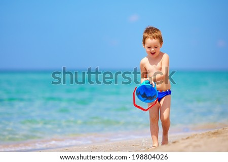 happy boy playing with toys on the beach - stock photo