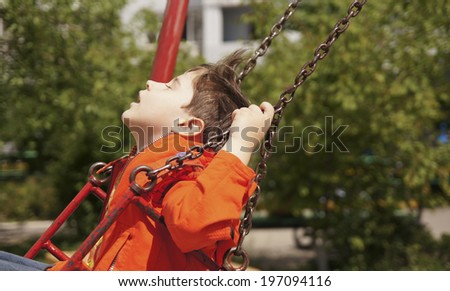 Happy boy riding on a swing at the playground