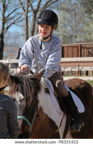 Happy boy seated on horseback participates in Hippo Therapy - stock photo