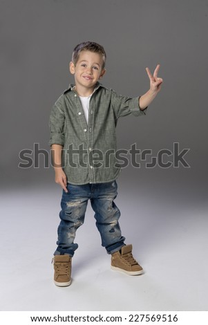 Happy boy showing victory sign   - stock photo