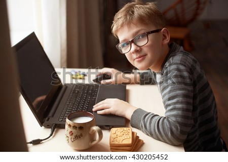 Happy boy sitting at his desk With laptop computer - stock photo