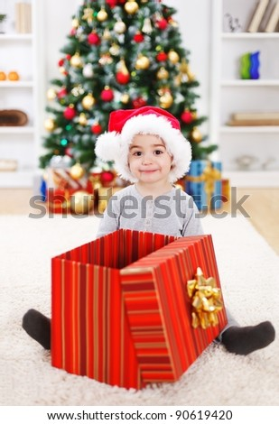 Happy boy sitting behind big open Christmas present box - stock photo