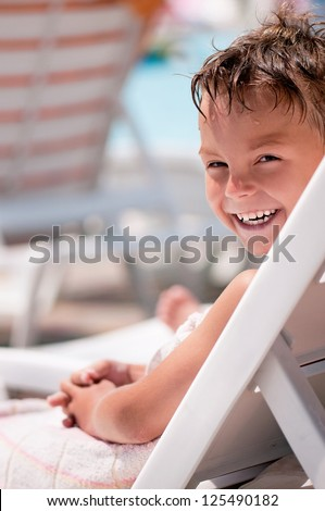 Happy boy sitting on a deck chair at the beach - stock photo