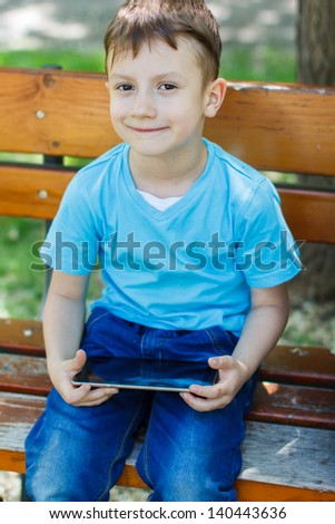 Happy boy sitting on bench with tablet, outdoors