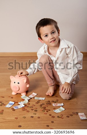 Happy boy sitting on the floor and collecting money in his piggy bank - stock photo